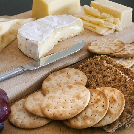Cheese platter with assorted cheeses served as an appetizer with water biscuits and wheat crackers on a buffet table